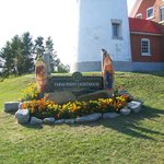 flower bed and sign in front of lighthouse