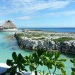 Vista del bar de playa a la caleta y el mar. Se ven un poco las habitaciones más lejanas