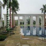 Pool bei Regen mit weihnachtlich geschmückten Palmen