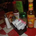 "Nice little table collection of Mexican hot sauces & red pepper flakes to ""heat up"" your meal!"