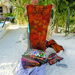 Local selling tapestries on beach near Belizean Shores