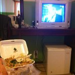 Inside my room eating fried rice and watching TV