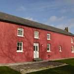 Cefnmeurig is a stone built Welsh longhouse painted a traditional Carmarthenshire red.