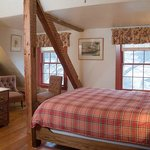 Room 14 on the third feel has a rustic feel with wood beams and a queen bed