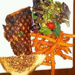 Cajun Salmon w/mixed greens & sweet potato fries.....on a paper plate.