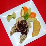 Grilled wahoo with sweet onion red wine reduction, roasted garlic potato puree, sauteed veg.