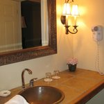 vanity and sink outside of the bathroom, between parlor and bedroom