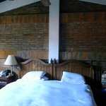 Brick above king-sized bed