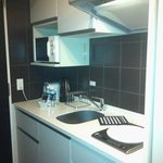Kitchen equiped with pots, pans, kettle, toaster, fridge, electric cook top an