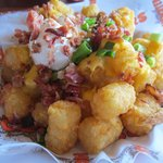 Tater Tots WIth Bacon Bits, Sour V+Cream and Green Onions.