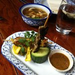 satay - beef and chicken with peanut sauce, behind: Tom yum soup