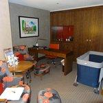 Coin salon avec lit pour bébé fourni par l'hôtel