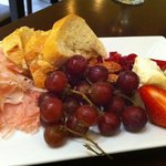 Cheese board with speck and fruit.