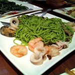 Handmade spinach noodles with seafood and mushrooms