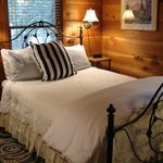 The Ponderosa shows Cedar finishes with Queen feather mattress pad bedding, comforter, and more.