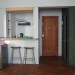 a porta de entrada e saída do quarto e a cozinha tipo bar
