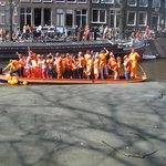 Boatfull of people celebrating Queens Day from Hotel Balcony