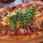 Breakfast pizza with bacon, potatoes, egg and arugula