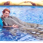 cuddles with dolphin in training pool