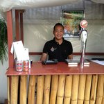 A smiling face behind the bar, adjacent to the pool