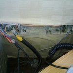 Electrical cables coming out of the wall behind night desk