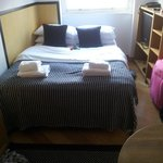Double bed, made nicely. Large TV and storage to the right.
