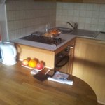 Breakfast bar with kettle, oven, sink and toaster stored away.