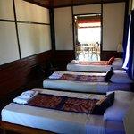 Chambre triple n°4, ouvrant sur la terrasse en bois et la vue sur le Mékong