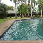 Het zwembad met de niet opgeruimde vulslang in het water