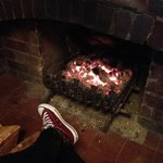 Warming my feet by the fire after a day walking in the Peak District.