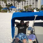 the hubby relaxing in a cabana with the hotel behind him