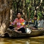 Locals on rowboats in flooed forest