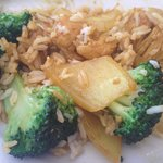 Curry Chicken dish mixed with steamed rice side and stir fried broccoli half-s