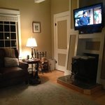 Multiple fire places and TV and leather coach and chair make for a cozy relaxi