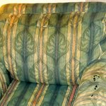 Old stained & worn out comfy chair & hassock.