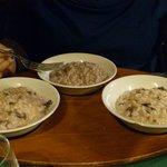 Tris di risotti servito su vassoio di legno