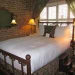 Room 154 w/ lovely exposed brick wall & queen-size bed