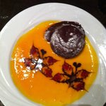 Chocolate volcano dessert with butterfly design in light peach syrup