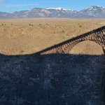 Shadow of the center-span arch cast on the far side gorge. Bighorn sheep barely visible in the s