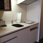 Kitchenette with bar fridge under hotplate. Good lighting.