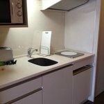 Kitchenette with bar fridge under hotplate. Good lighting.