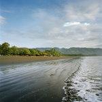 Enjoy the sound of waves hitting the volcanic sandy beach.