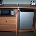 Dresser with microwave and fridge next to desk