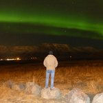 Spetacular northern lights over the mountains next to Reykjavik