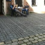 A couple of guys sitting across the street from hotel where several business f