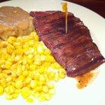 flat iron steak cooked medium rare with mashed potato and corn