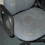 Desk chair with stains and worn.