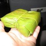 Boxed breakfast sandwich wrapped in banana leaf