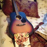The guitar and the offbeat magazine ready on the bed