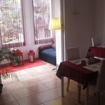 Tables, a window, red curtains. Also there are paper reviews of visitors on th